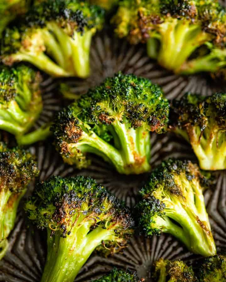 up close overhead view of roasted broccoli on a baking sheet