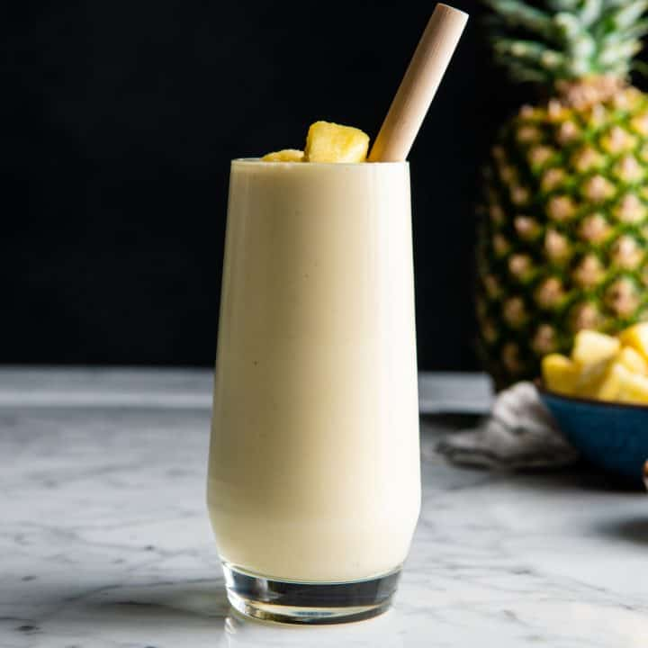 Healthy Pineapple Smoothie in a glass with a straw and pineapple pieces on top