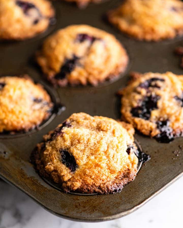 front view of blueberry muffins in a muffin tin after baking
