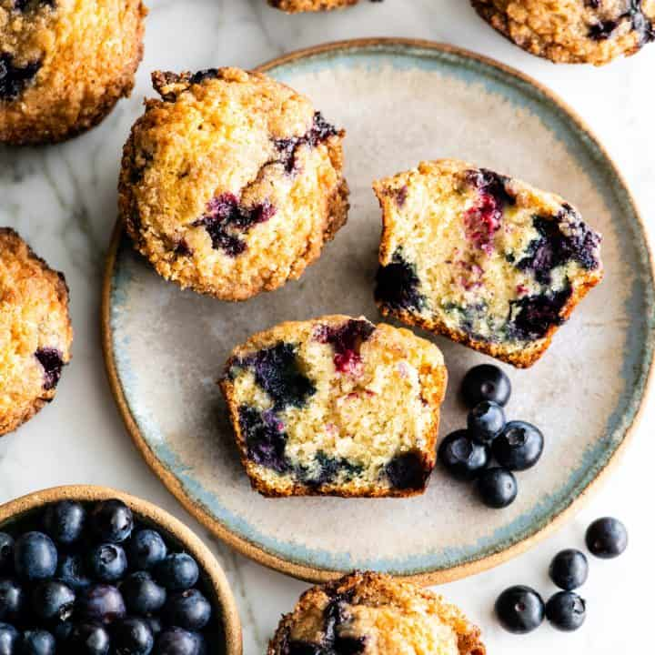 overhead view of a blueberry muffin cut in half with other whole muffins around it