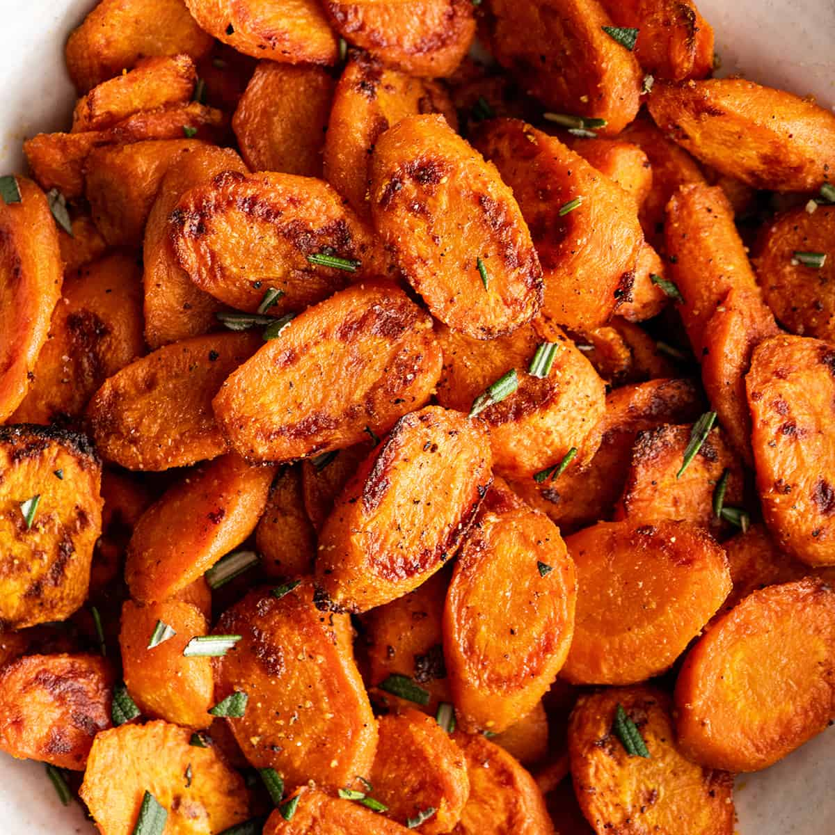 up close overhead view of Oven Roasted Carrots in a bowl garnished with herbs