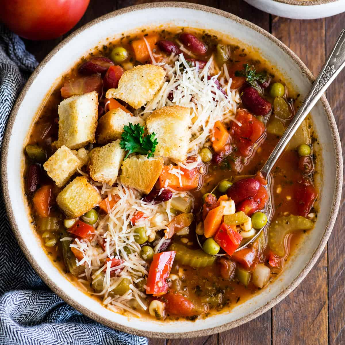 overhead view of a bowl of homemade vegetable soup topped with croutons and cheese with a spoon in it