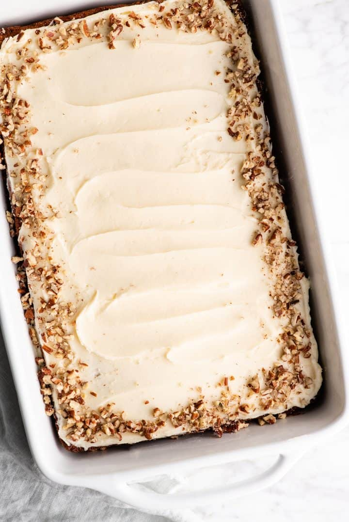 overhead view of a frosted banana cake in a pan with nuts around the edge