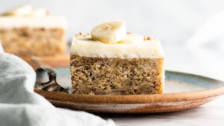 front view of a slice of banana cake with cream cheese frosting