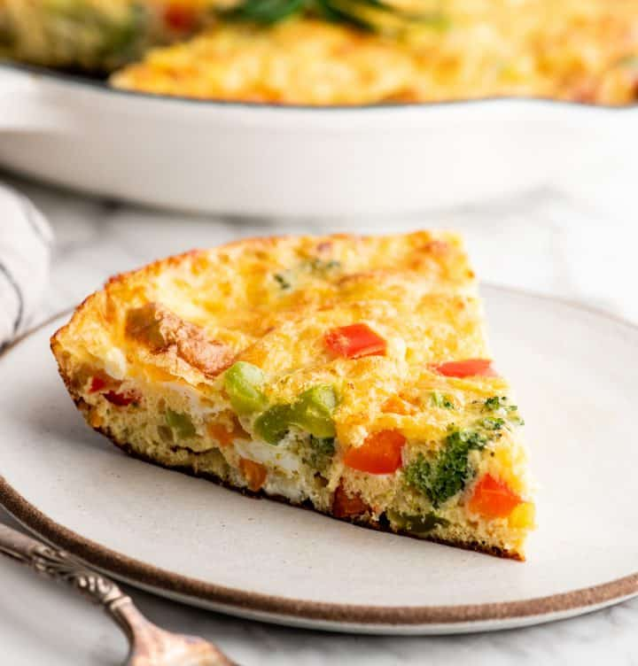 front view of a slice of vegetable frittata on a plate