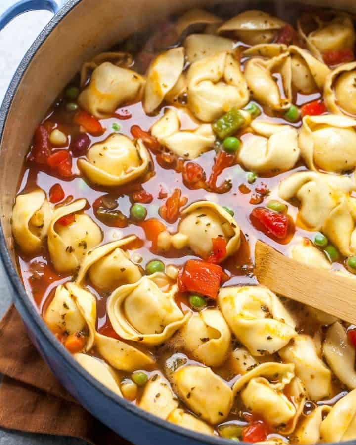 tortellini soup in a pot with a wooden spoon