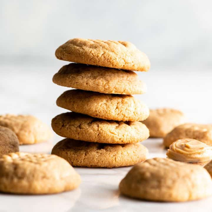 front view of a stack of 4 flourless peanut butter cookies with other cookies around the stack on the table