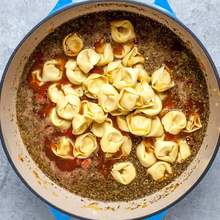 overhead photo showing how to make tortellini soup adding tortellini