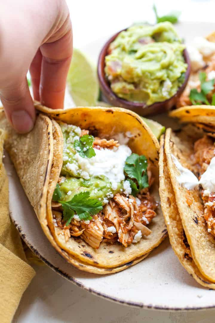 front view of a hand holding a Mexican shredded chicken taco