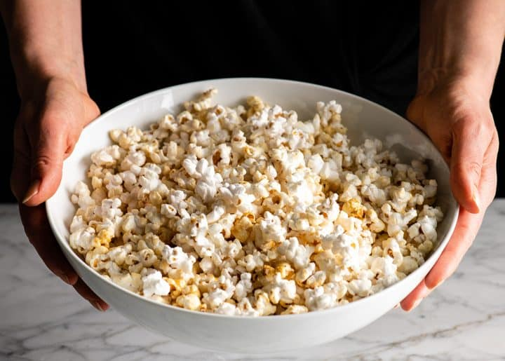 Front view of someone holding a large bowl of homemade kettle corn