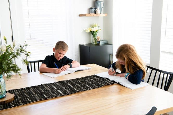 two children practicing handwriting at a table