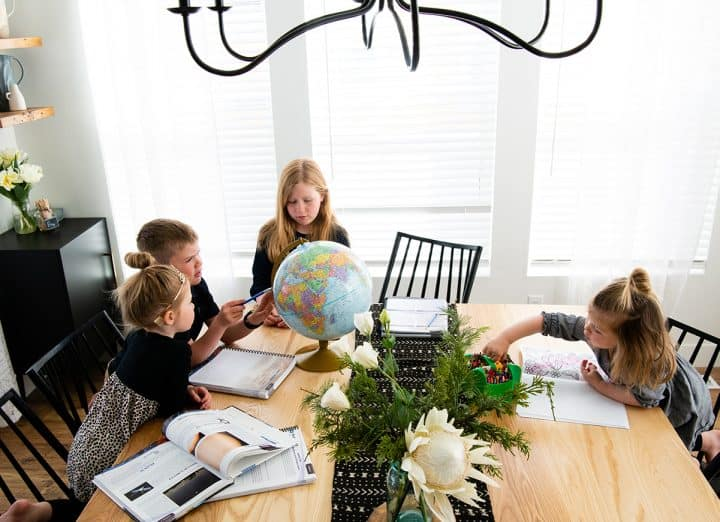 four kids doing homeschool at a table