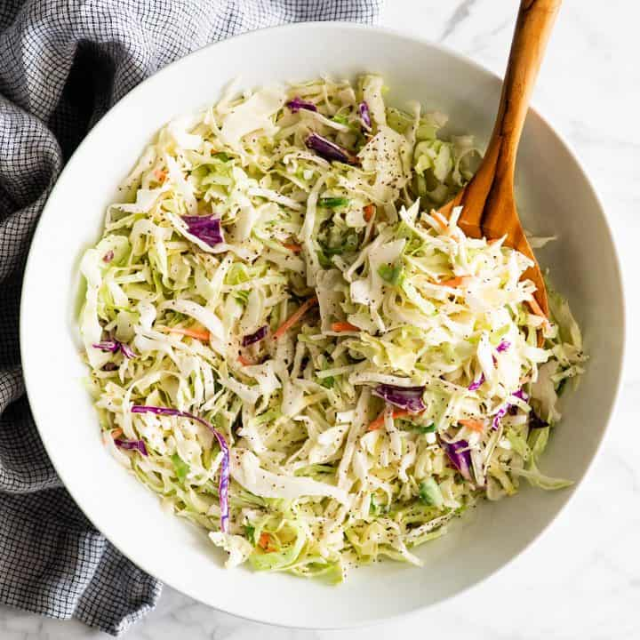 spoon taking a scoop of coleslaw out of a large bowl