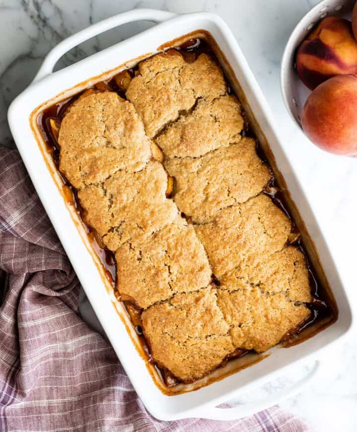 overhead view of a baked peach cobbler in a white baking dish