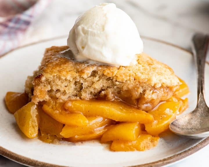 front view of a piece of peach cobbler on a plate with vanilla ice cream on top