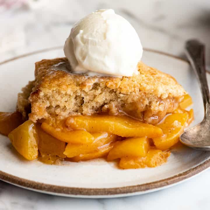 piece of peach cobbler with ice cream on top on a plate