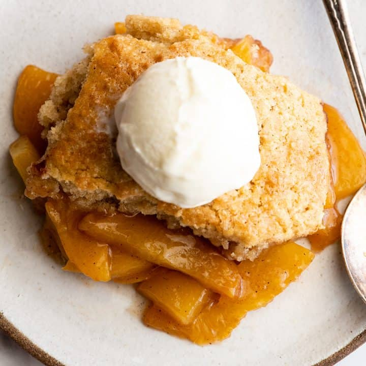 overhead view of a piece of peach cobbler with vanilla ice cream on top on a plate