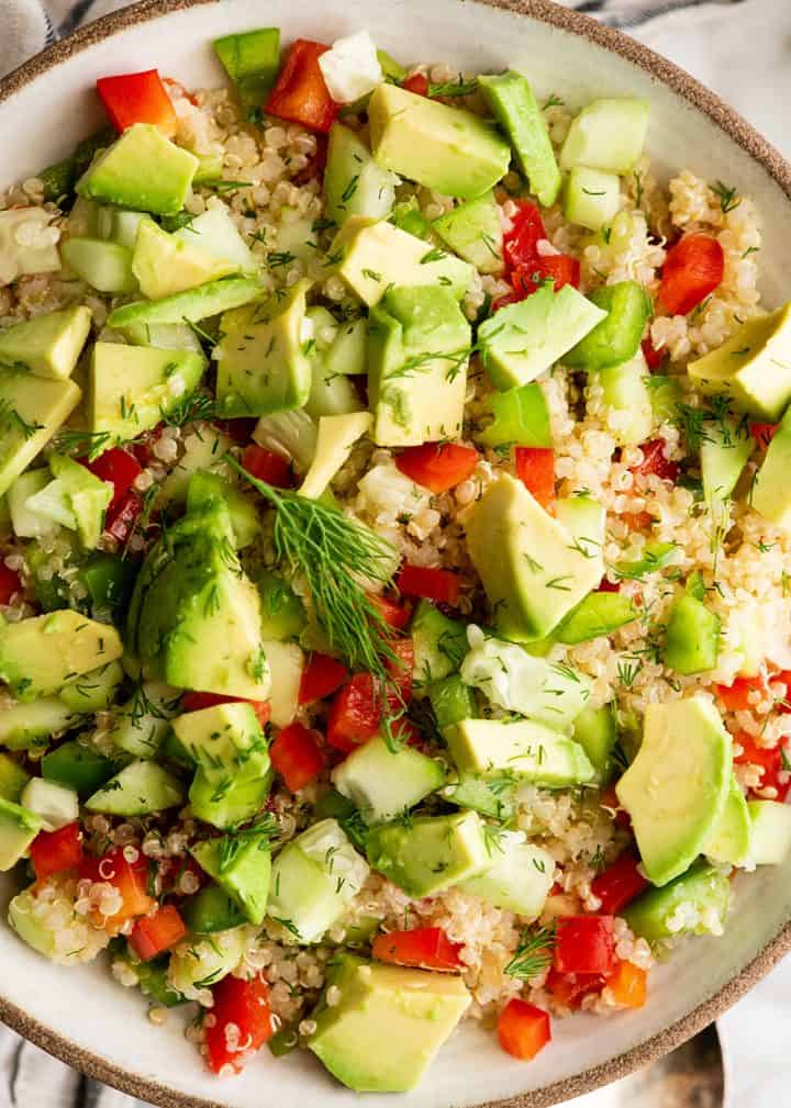 up close overhead view of a bowl of quinoa salad garnished with fresh dill