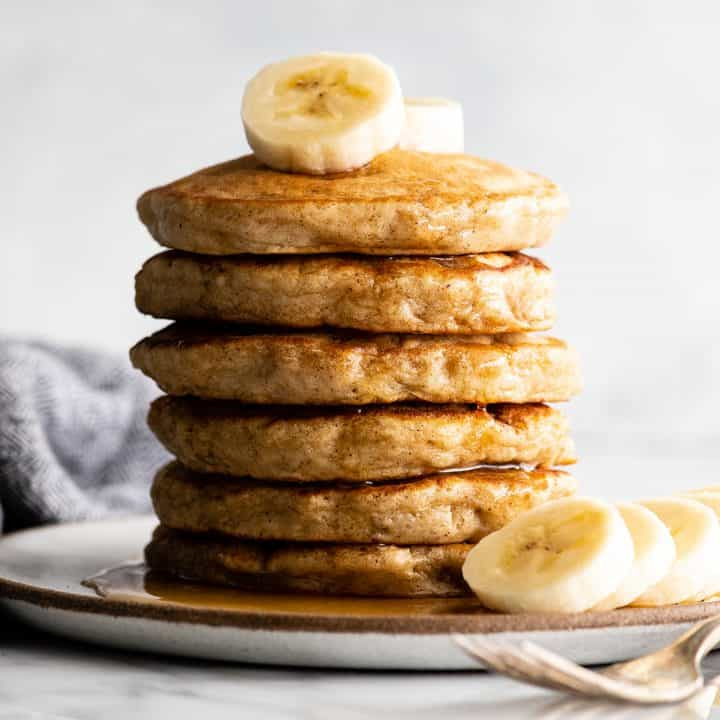 front view of a stack of 6 banana pancakes with syrup and sliced bananas