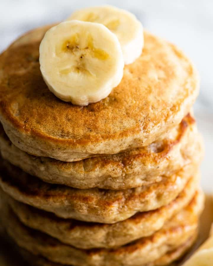 overhead view of a stack of 6 banana pancakes with sliced bananas