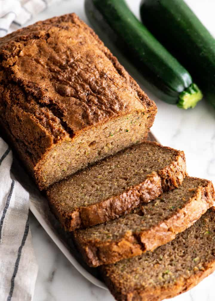 front view of a loaf of zucchini bread with 3 slices cut