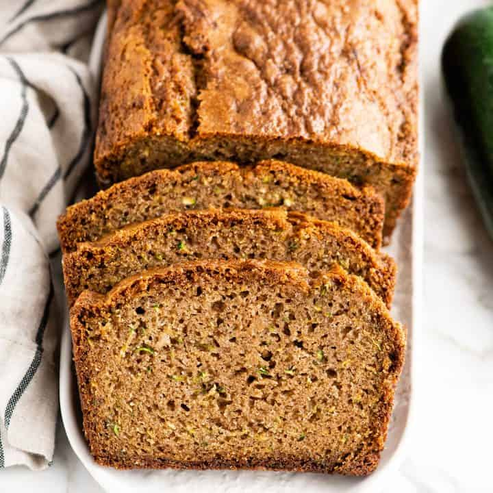 front view of a loaf of zucchini bread with three slices cut