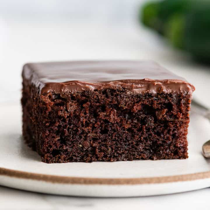 front view of a piece of chocolate zucchini cake with chocolate ganache