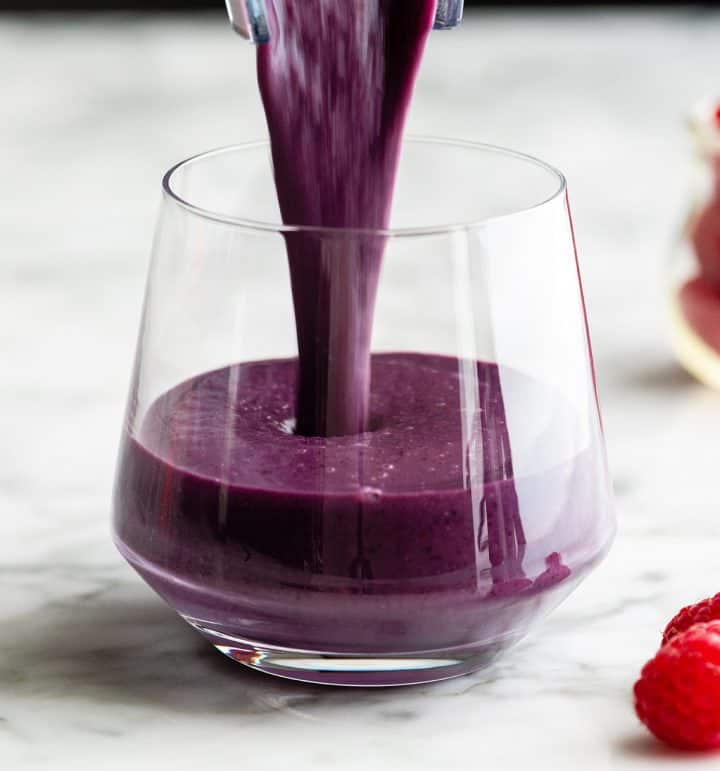berry smoothie being poured into a glass cup