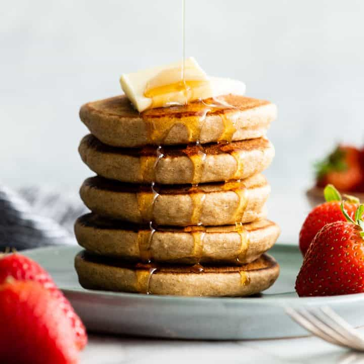 front view of a stack of 5 banana oatmeal pancakes with syrup pouring on the top