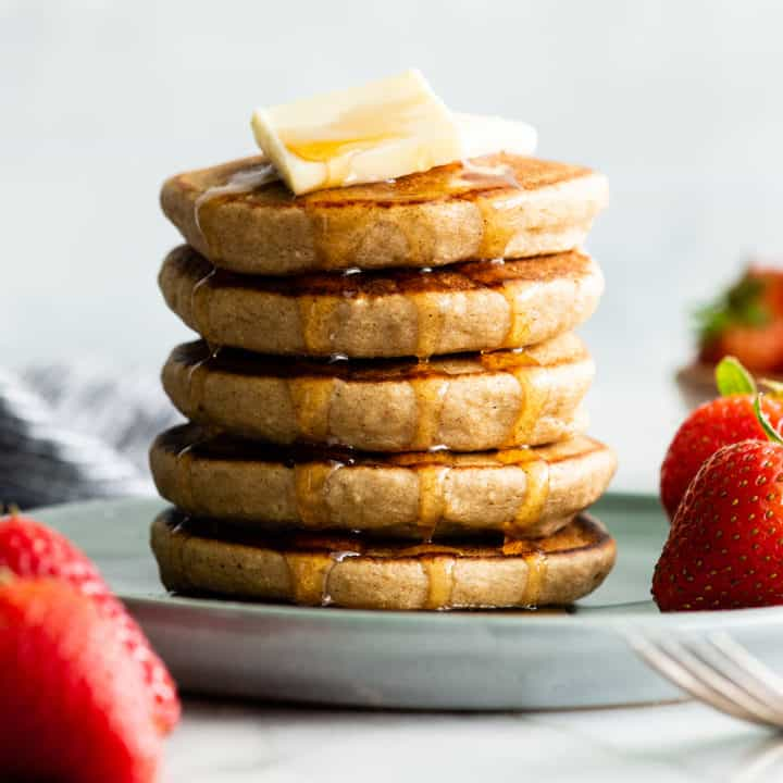Front view of a stack of 5 banana oatmeal pancakes with butter and syrup