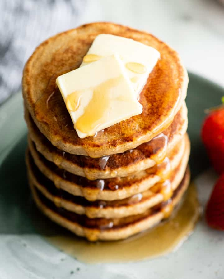 overhead view of a stack of 5 banana oat pancakes with butter and syrup