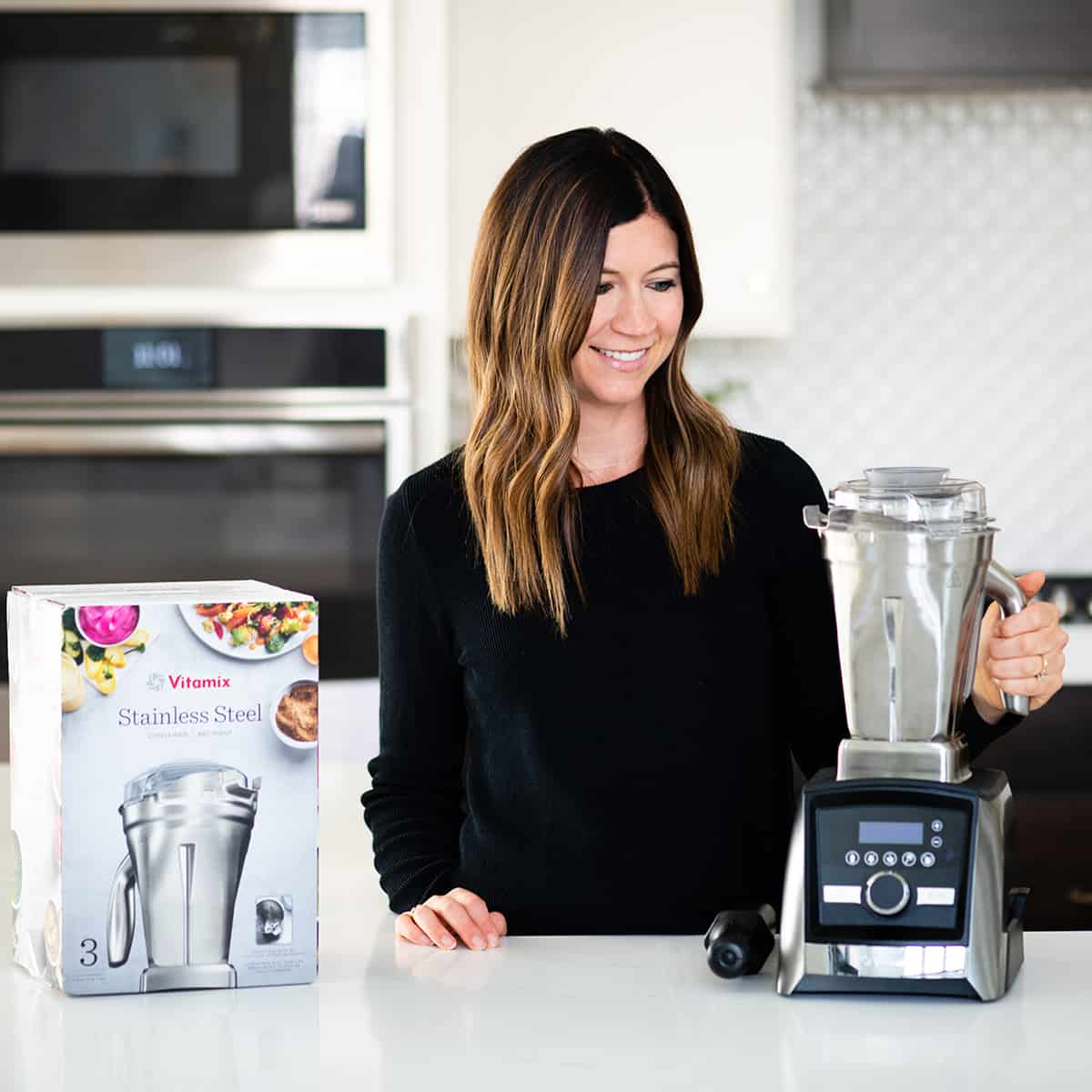 front view of woman holding Vitamix stainless steel container