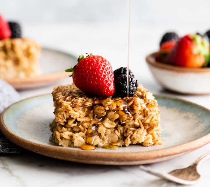 front view of a piece of baked oatmeal with berries and maple syrup