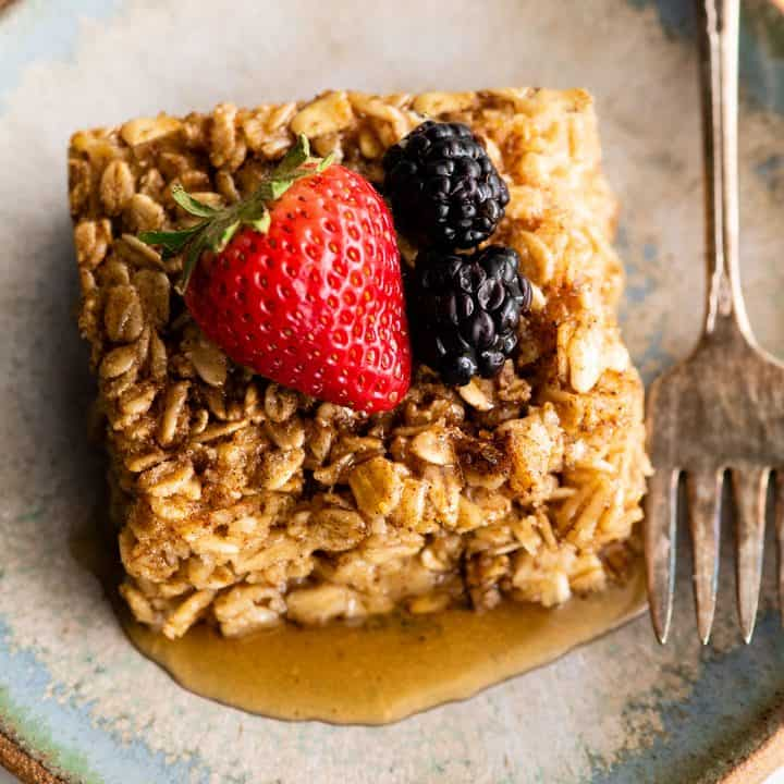 overhead view of a piece of Baked Oatmeal with berries and maple syrup
