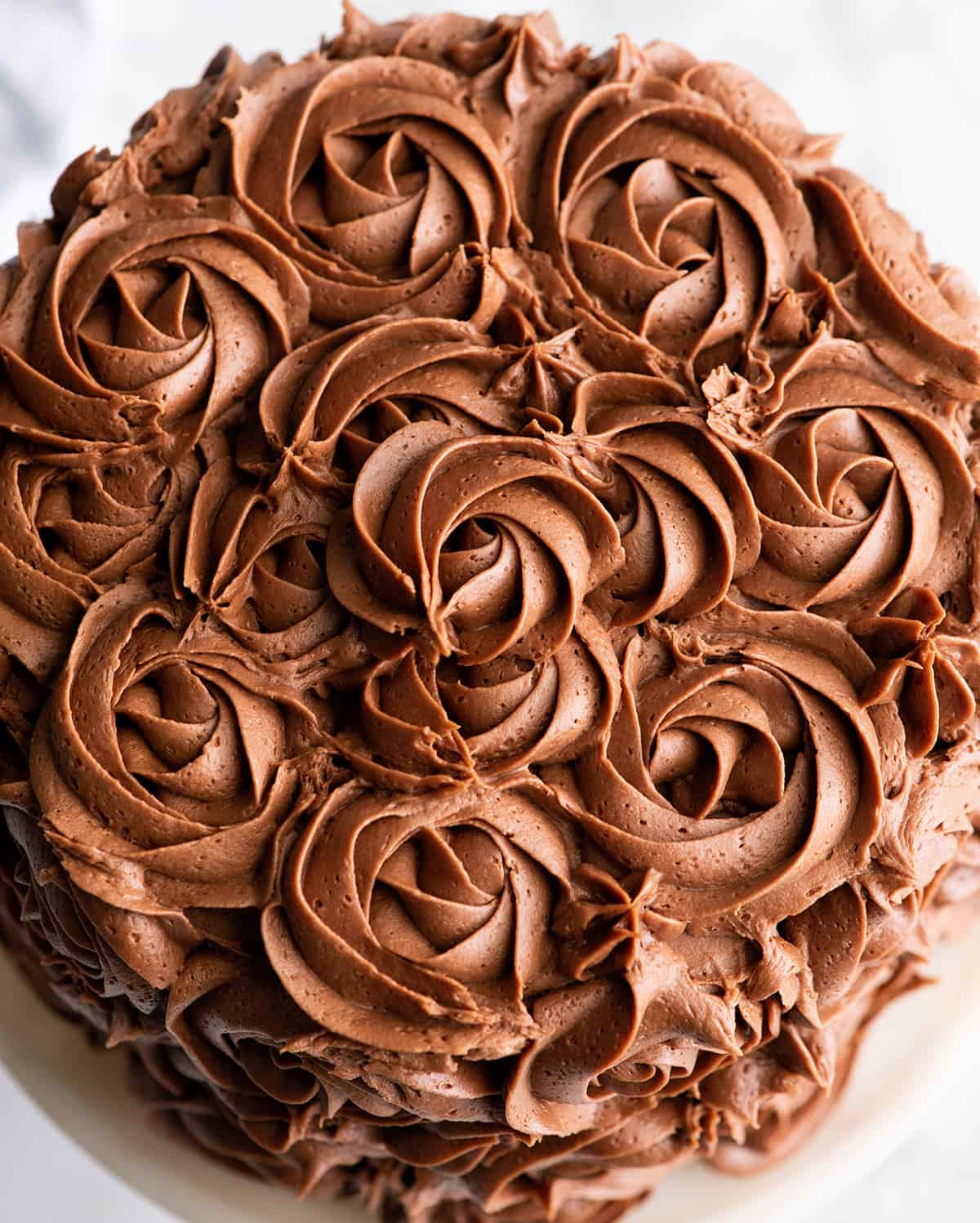 overhead photo of a rosette cake frosting with chocolate frosting
