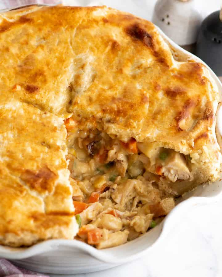 chicken pot pie in a pie dish with one piece cut out
