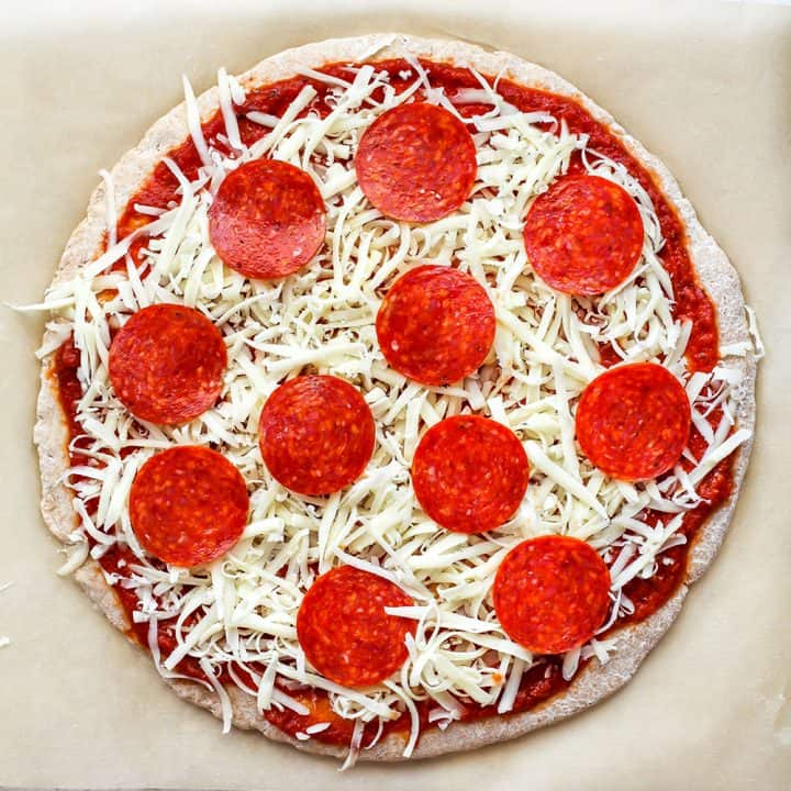 overhead photo showing whole wheat pizza crust with toppings before baking