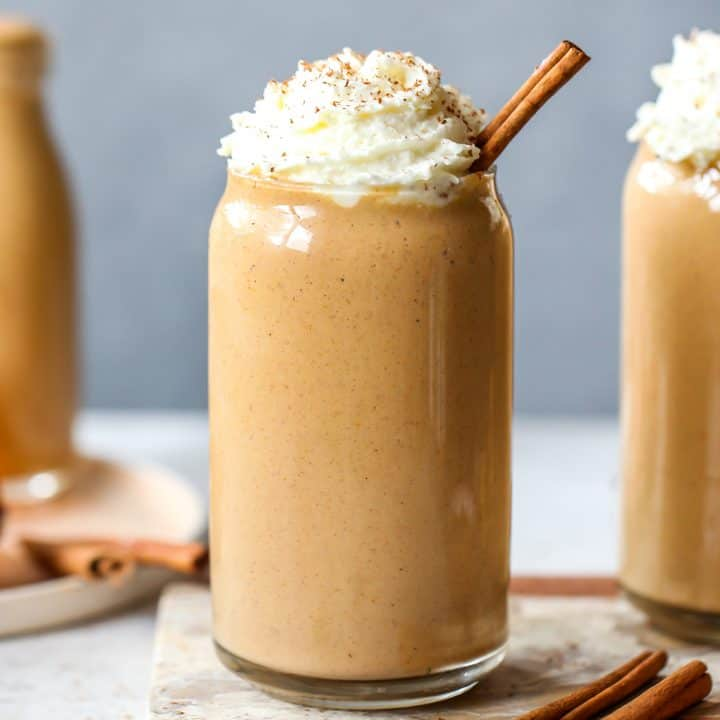 front view of a pumpkin smoothie in a glass with whipped cream on top