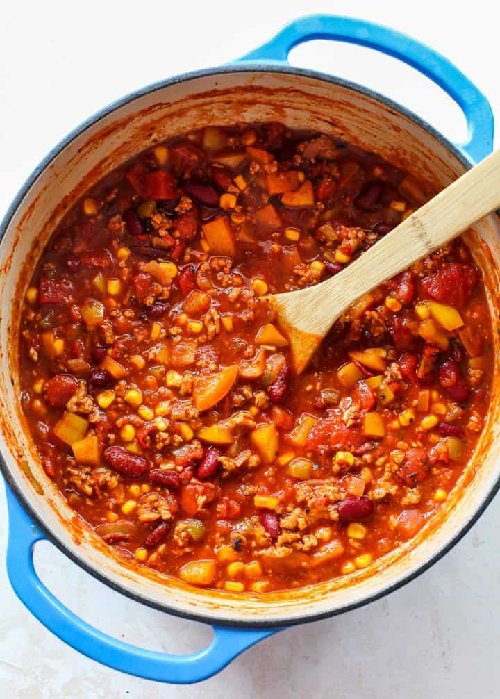 overhead photo of a pot of turkey chili with a spoon