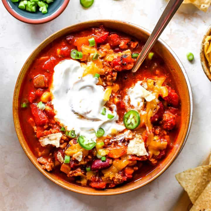 Overhead photo of a bowl of turkey chili with sour cream, cheese and green onions
