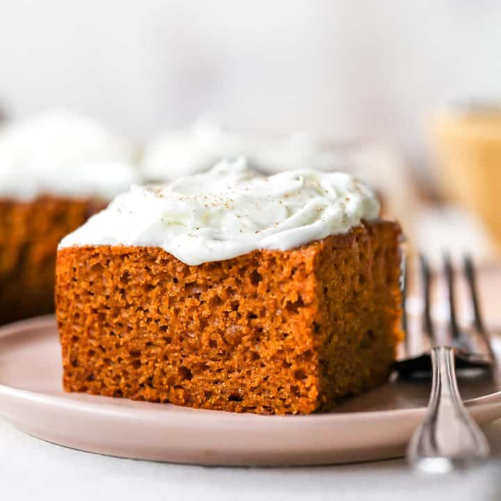 front view of a piece of Pumpkin Cake on a plate with cream cheese frosting