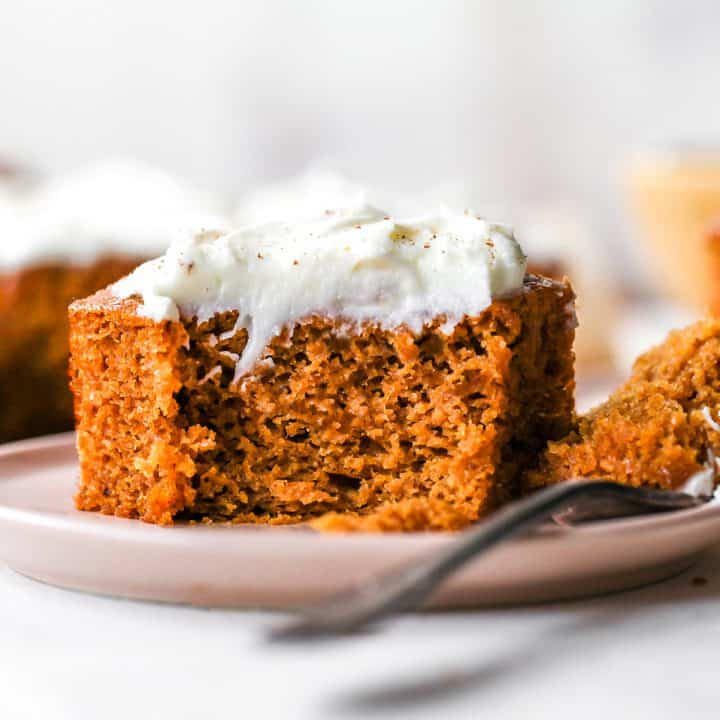 front photo of a piece of Pumpkin Spice Cake on a plate with a bite taken out of it