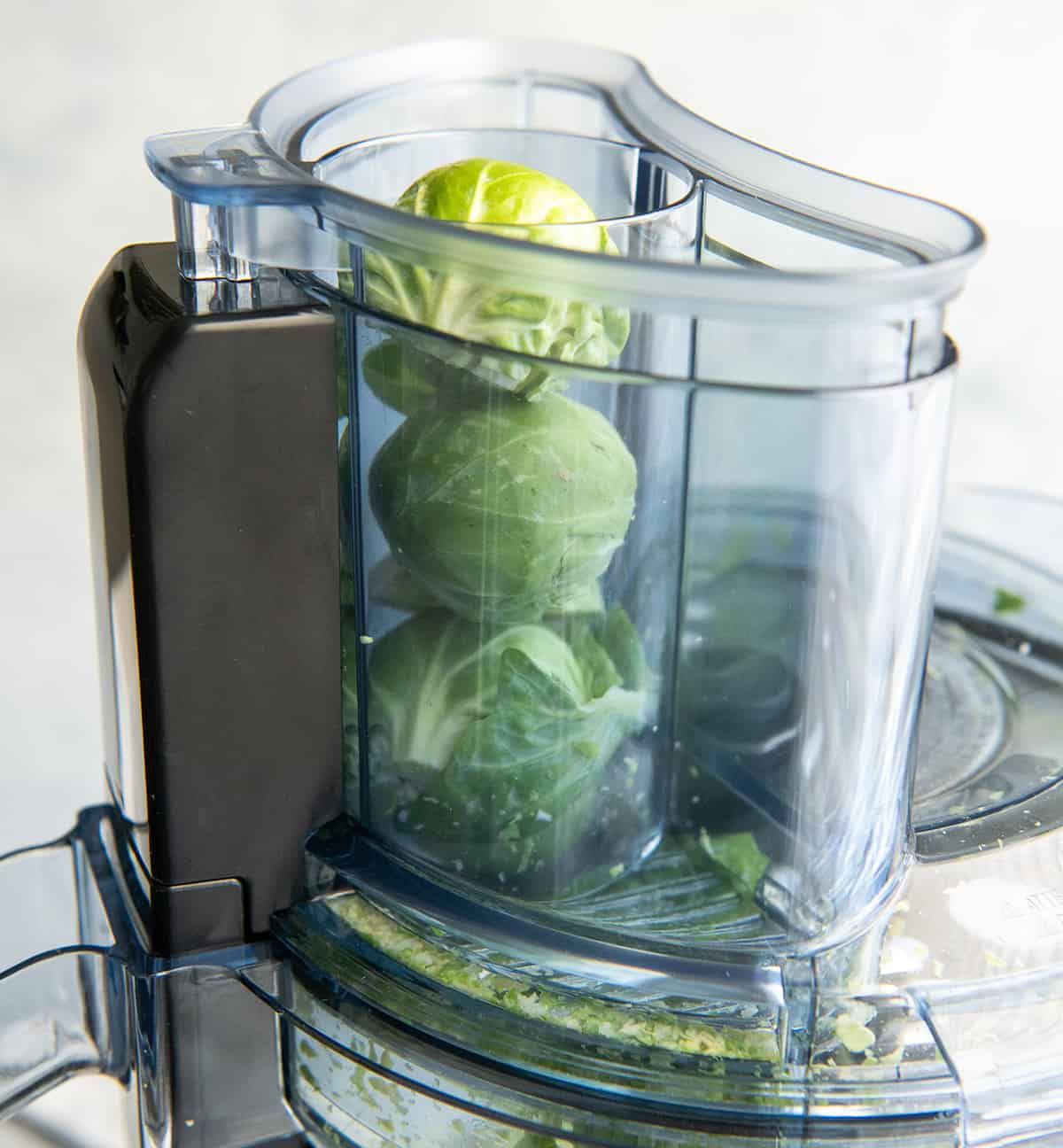 Brussels sprouts in the small food chute of a Vitamix food processor