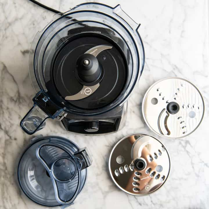 Overhead view of the Vitamix food processor with the multi-use blade attached and the other discs around it
