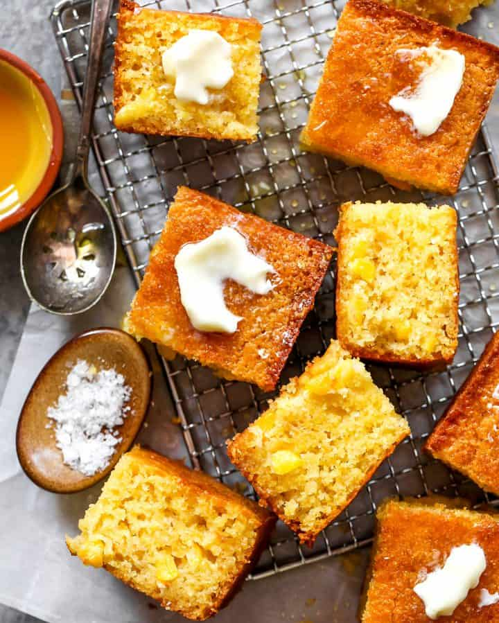 overhead view of the best homemade cornbread cut into squares with butter