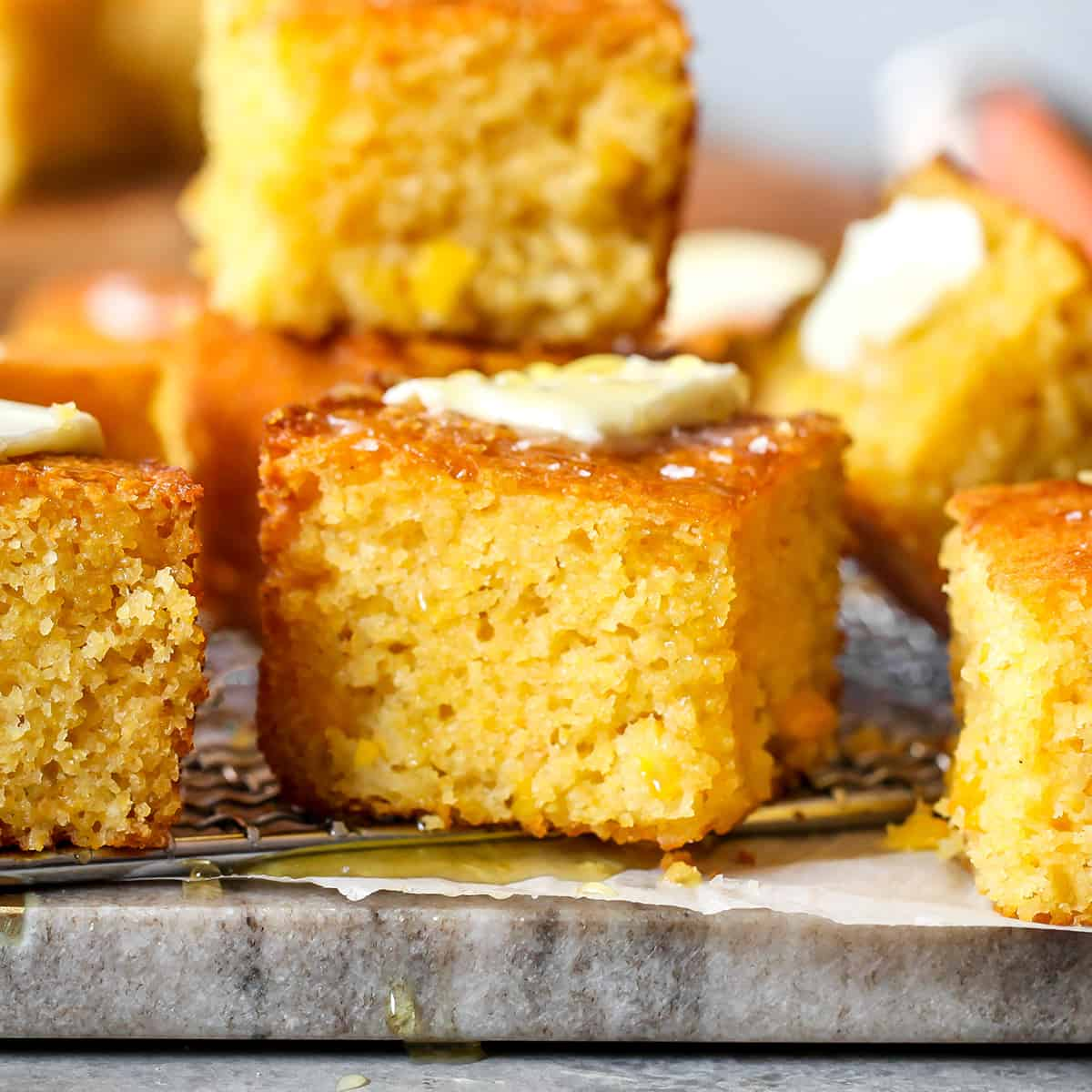 front view of slices of cornbread with melting butter on top