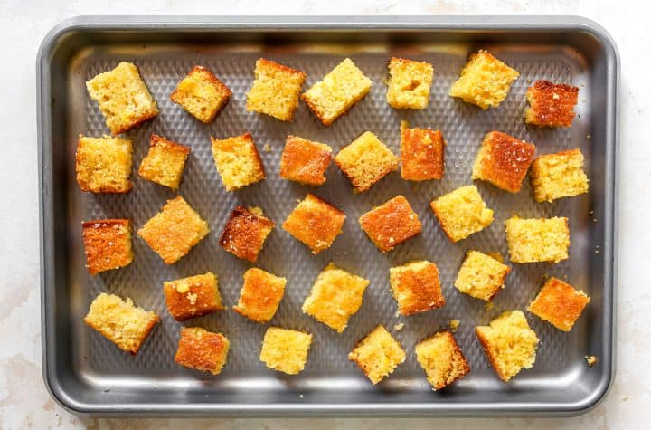 overhead photo showing Cornbread Croutons on a baking sheet before being baked