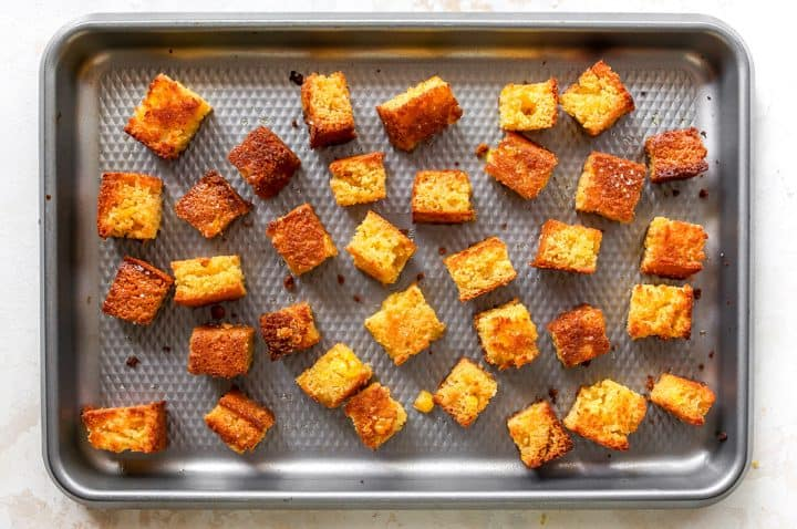 overhead photo of Cornbread Croutons on a baking sheet after being baked