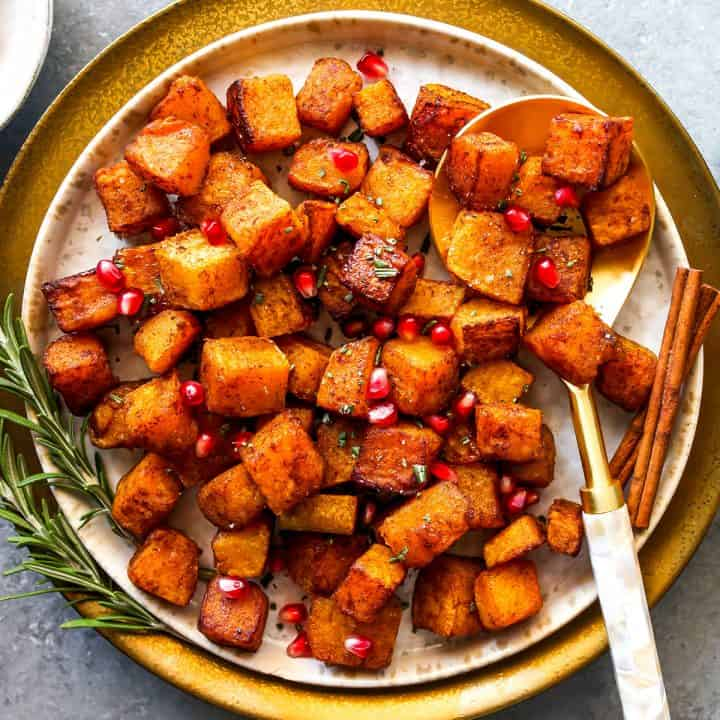 overhead view of cinnamon roasted butternut squash on a plate with pomegranates and rosemary