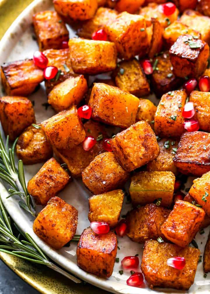 up close overhead view of Cinnamon Roasted Butternut Squash on a plate with pomegranates and rosemary